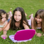 Three little girl playing with toy computer in grass