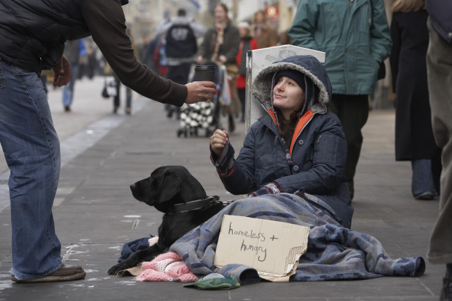 Person giving coffee to homeless woman